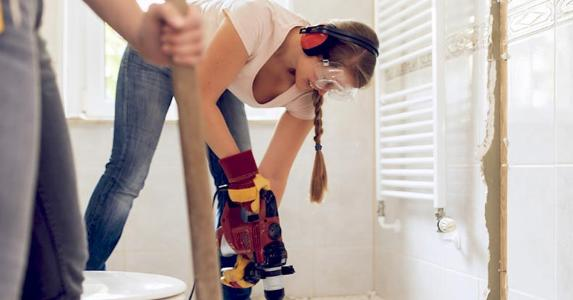 Young woman drilling tile floors during bath renovation | Guido Mieth/DigitalVision/Getty Images
